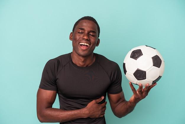 Jovem afro-americano jogando futebol isolado no fundo azul, rindo e se divertindo.