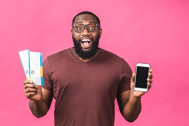 Jovem afro-americano negro segurando os bilhetes do cartão de embarque isolados sobre o fundo rosa. usando o celular.