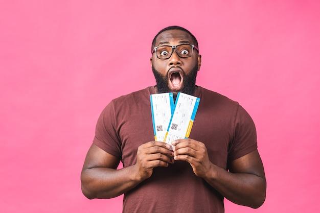 Jovem afro-americano negro segurando os bilhetes do cartão de embarque isolados sobre o fundo rosa.