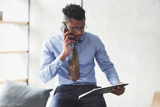 Jovem afro-americano ocupado conversando ao telefone