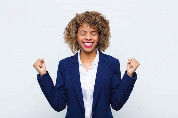 Jovem afro-americano olhando extremamente feliz e surpreso, comemorando o sucesso, gritando e pulando contra a parede plana