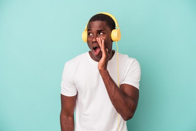Jovem afro-americano ouvindo música isolada em fundo azul, gritando e segurando a palma da mão perto da boca aberta.