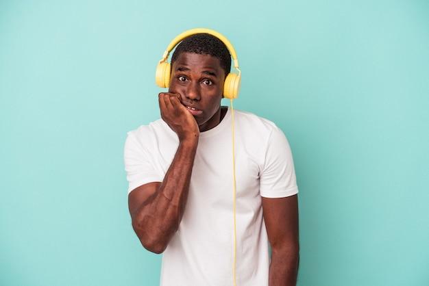 Jovem afro-americano ouvindo música isolada em fundo azul, roendo as unhas, nervoso e muito ansioso.