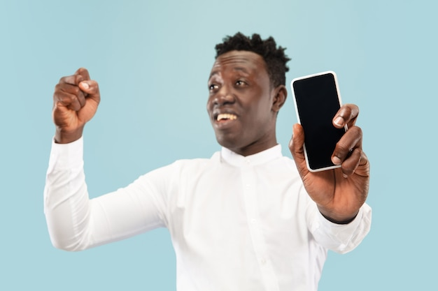 Jovem afro-americano posando com smartphone isolado em um fundo azul do estúdio, expressão facial. belo retrato masculino de meio comprimento. conceito de emoções humanas, expressão facial.