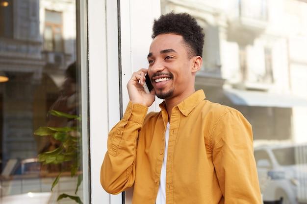 Jovem afro-americano positivo, veste camisa amarela, andando na rua e falando ao telefone com, amplamente sorrindo e desviando o olhar, curtindo o dia ensolarado.
