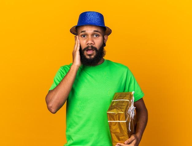 Jovem afro-americano preocupado com um chapéu de festa segurando uma caixa de presente e colocando a mão na bochecha isolada em uma parede laranja