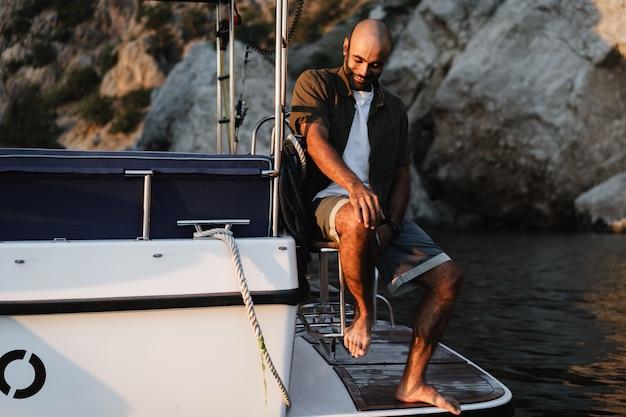 Jovem afro-americano relaxando em um veleiro em mar aberto ao pôr do sol