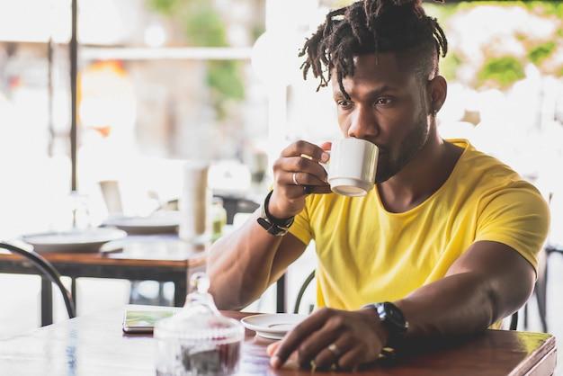 Jovem afro-americano relaxando enquanto bebe uma xícara de café em uma cafeteria.