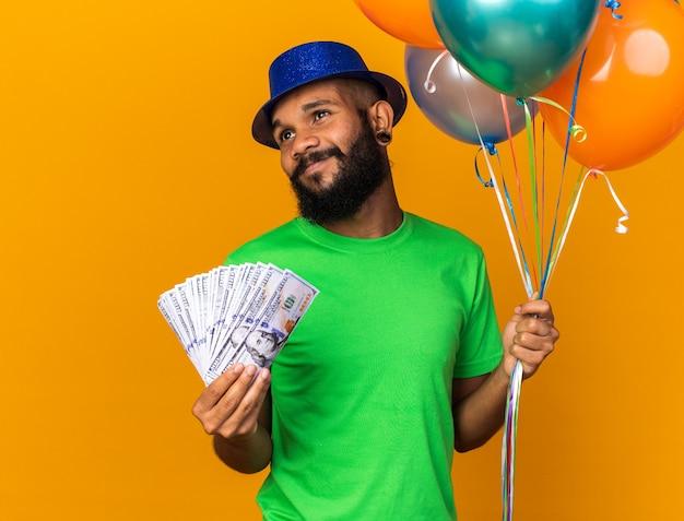 Jovem afro-americano satisfeito com um chapéu de festa segurando balões e dinheiro isolado na parede laranja