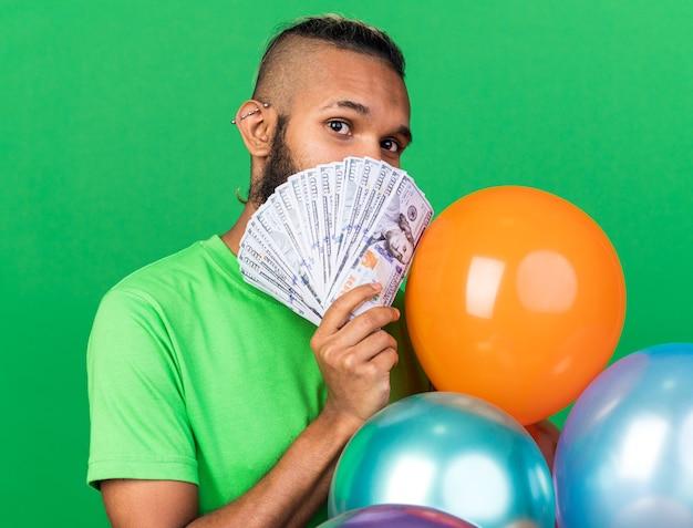 Jovem afro-americano satisfeito com uma camiseta verde em pé atrás de balões, cobrindo o rosto com dinheiro