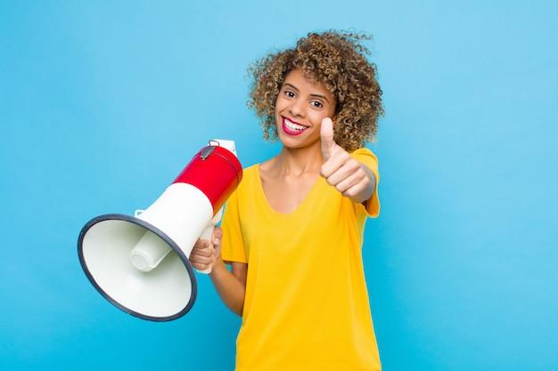 Jovem afro-americano se sentindo orgulhoso, despreocupado, confiante e feliz, sorrindo positivamente com os polegares para cima com um megafone