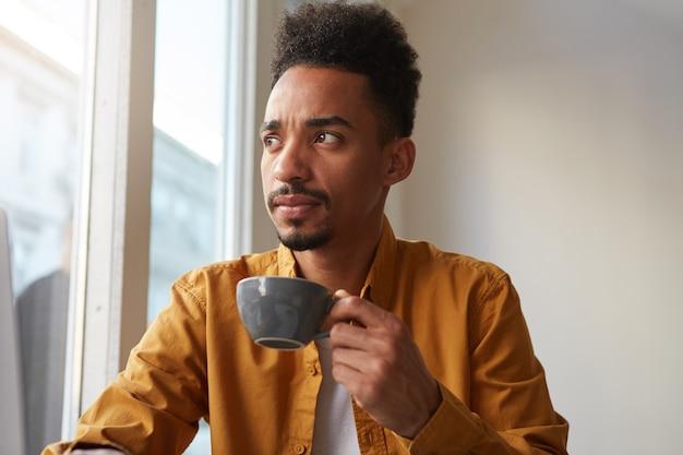 Jovem afro-americano se veste de camisa amarela, senta-se à mesa em um café e bebe um café aromático, pensando onde ir neste fim de semana. olhando pensativamente para a distância.