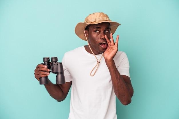 Jovem afro-americano segurando binóculos isolados em um fundo azul está contando uma notícia secreta de frenagem e olhando para o lado