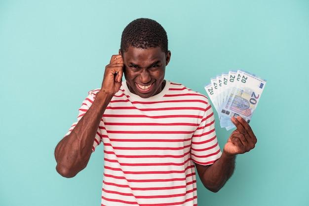 Jovem afro-americano segurando notas de banco isoladas em um fundo azul, cobrindo as orelhas com as mãos.
