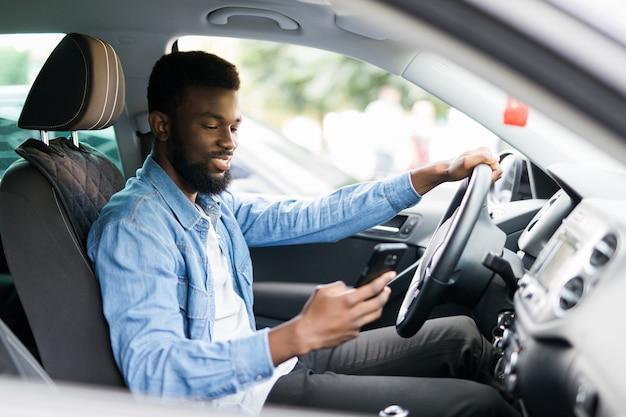 Jovem afro-americano segurando seu telefone enquanto dirige seu carro