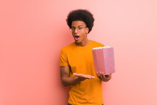 Jovem afro-americano segurando um balde de pipoca segurando algo na palma da mão