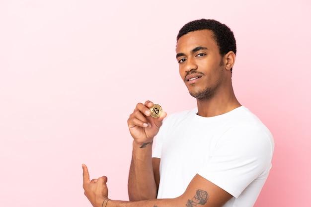 Jovem afro-americano segurando um bitcoin sobre um fundo rosa isolado apontando para trás