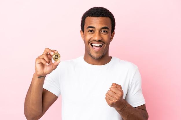 Jovem afro-americano segurando um bitcoin sobre um fundo rosa isolado, comemorando a vitória na posição de vencedor