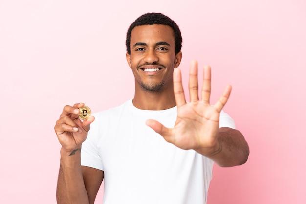 Jovem afro-americano segurando um bitcoin sobre um fundo rosa isolado, contando cinco com os dedos