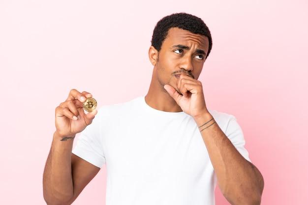 Jovem afro-americano segurando um bitcoin sobre um fundo rosa isolado e olhando para cima
