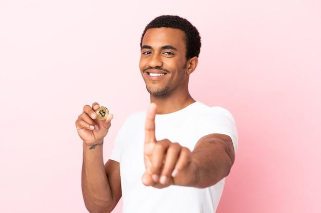 Jovem afro-americano segurando um bitcoin sobre um fundo rosa isolado, mostrando e levantando um dedo