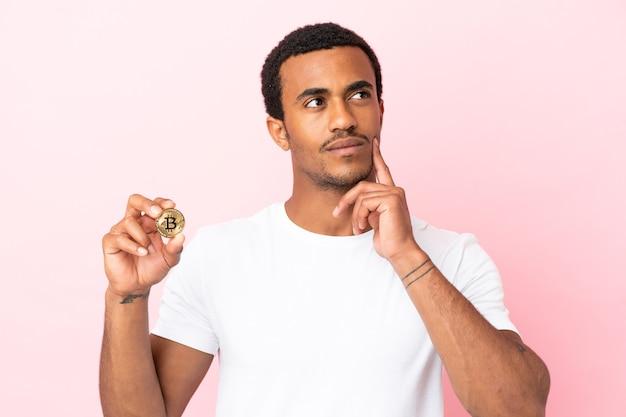 Jovem afro-americano segurando um bitcoin sobre um fundo rosa isolado, pensando em uma ideia enquanto olha para cima