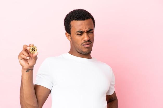 Jovem afro-americano segurando um bitcoin sobre um fundo rosa isolado, sofrendo de dor nas costas por ter feito um esforço