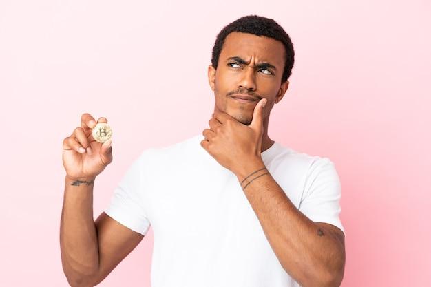 Jovem afro-americano segurando um bitcoin sobre um fundo rosa isolado, tendo dúvidas e pensando