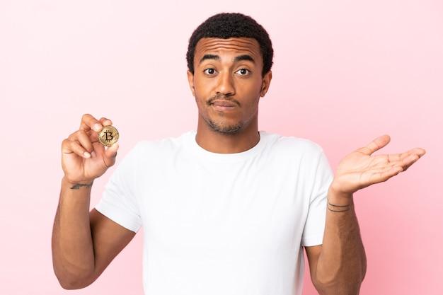 Jovem afro-americano segurando um bitcoin sobre um fundo rosa isolado, tendo dúvidas enquanto levanta as mãos