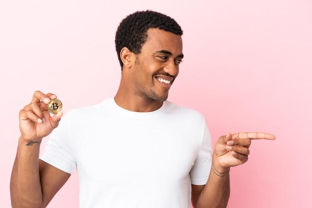Jovem afro-americano segurando um bitcoin sobre uma parede rosa isolada, apontando o dedo para o lado e apresentando um produto