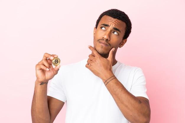 Jovem afro-americano segurando um bitcoin sobre uma superfície rosa isolada com dúvidas