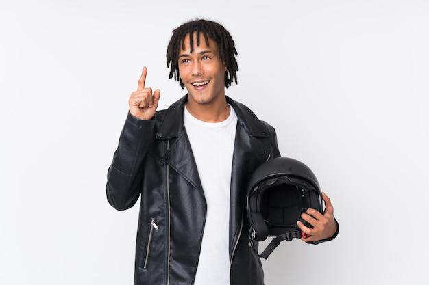 Jovem afro-americano segurando um capacete de moto isolado no branco com a intenção de perceber a solução enquanto levanta um dedo