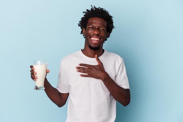 Jovem afro-americano segurando um copo de leite isolado sobre fundo azul ri alto, mantendo a mão no peito.