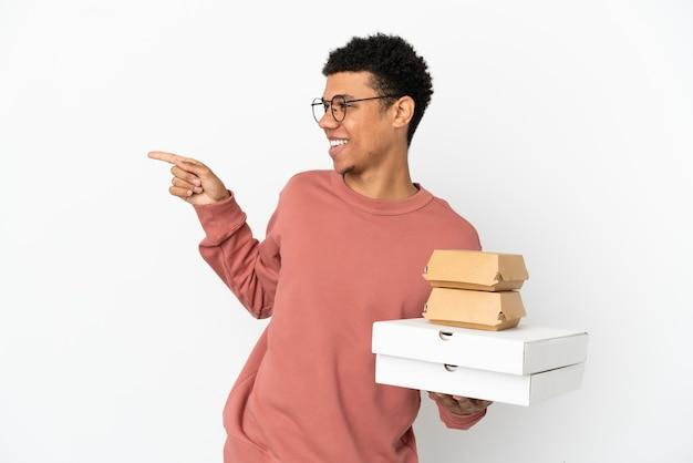 Jovem afro-americano segurando um hambúrguer e pizzas isoladas no fundo branco, apontando o dedo para o lado e apresentando um produto
