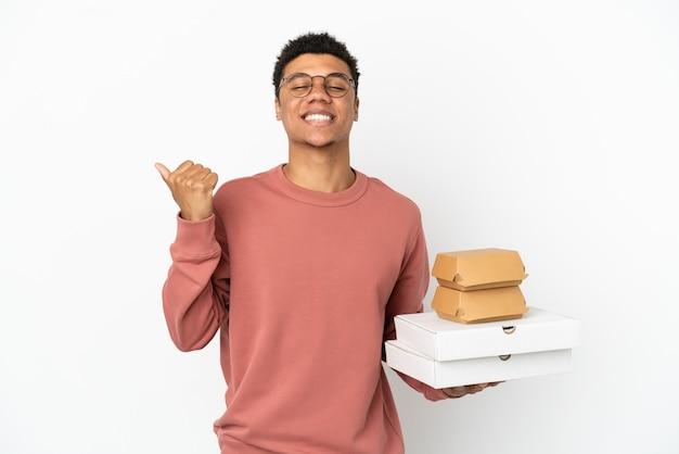 Jovem afro-americano segurando um hambúrguer e pizzas isoladas no fundo branco apontando para o lado para apresentar um produto