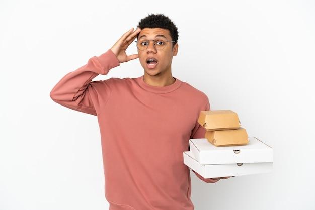 Jovem afro-americano segurando um hambúrguer e pizzas isoladas no fundo branco com expressão de surpresa