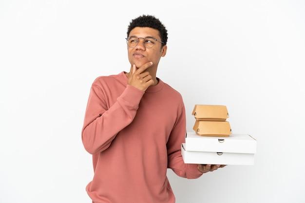 Jovem afro-americano segurando um hambúrguer e pizzas isoladas no fundo branco e olhando para cima