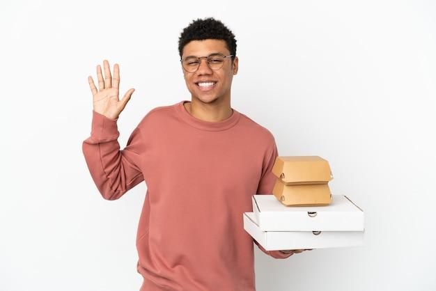 Jovem afro-americano segurando um hambúrguer e pizzas isoladas no fundo branco e saudando com a mão com uma expressão feliz
