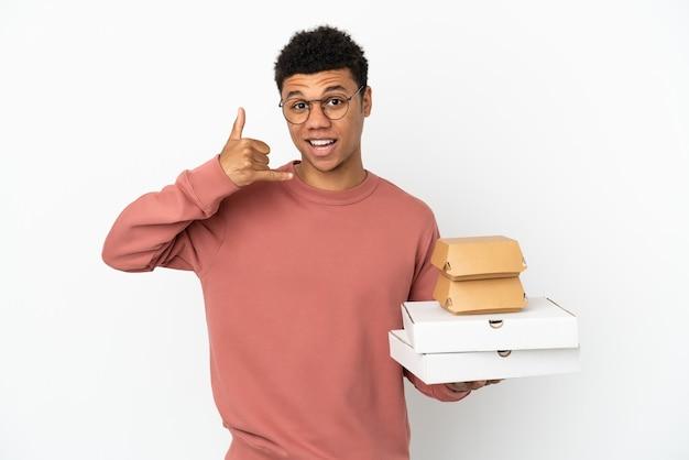 Jovem afro-americano segurando um hambúrguer e pizzas isoladas no fundo branco, fazendo gesto de telefone. ligue-me de volta sinal