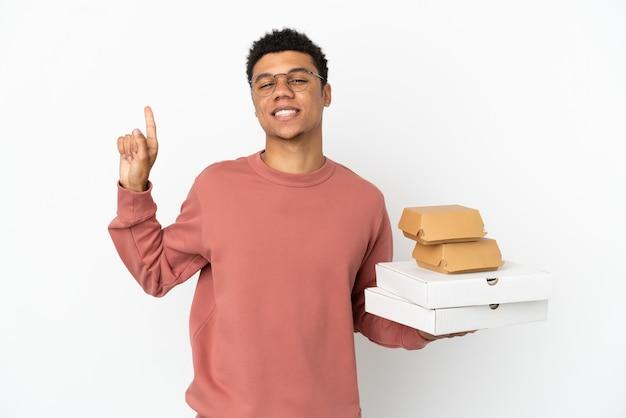 Jovem afro-americano segurando um hambúrguer e pizzas isoladas no fundo branco, mostrando e levantando um dedo em sinal dos melhores