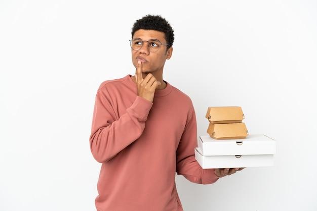 Jovem afro-americano segurando um hambúrguer e pizzas isoladas no fundo branco, tendo dúvidas enquanto olha para cima