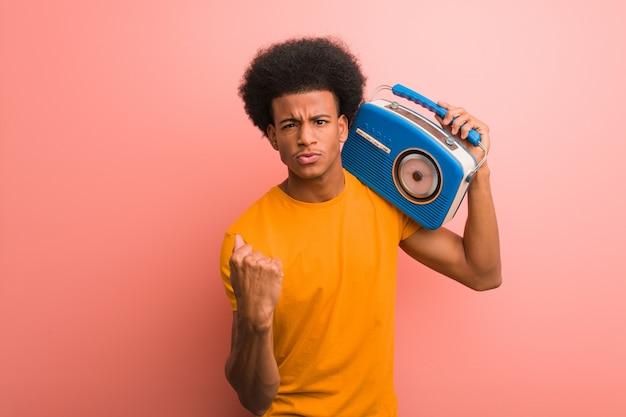 Jovem afro-americano segurando um rádio vintage, mostrando o punho para a frente, expressão de raiva