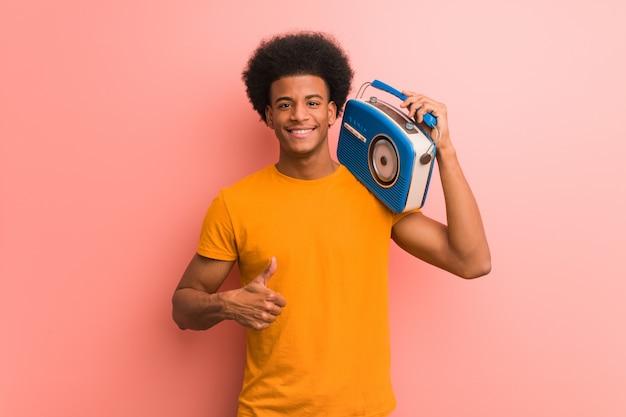 Jovem afro-americano segurando um rádio vintage sorrindo e levantando o polegar