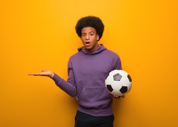Jovem afro-americano segurando uma bola de futebol segurando algo na palma da mão
