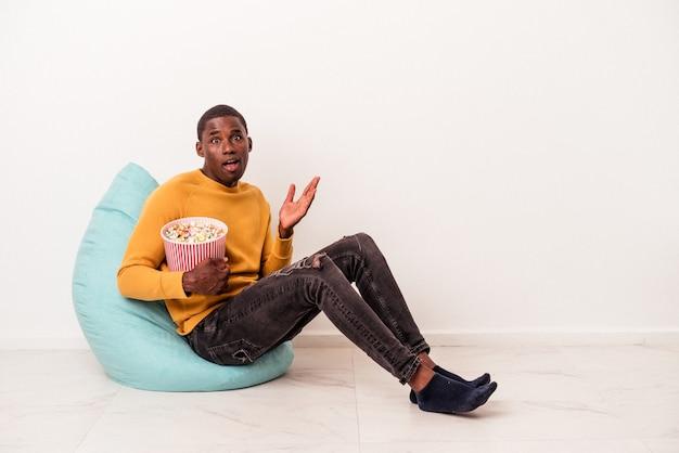 Jovem afro-americano sentado em um puff comendo pipoca isolada no fundo branco surpreso e chocado.