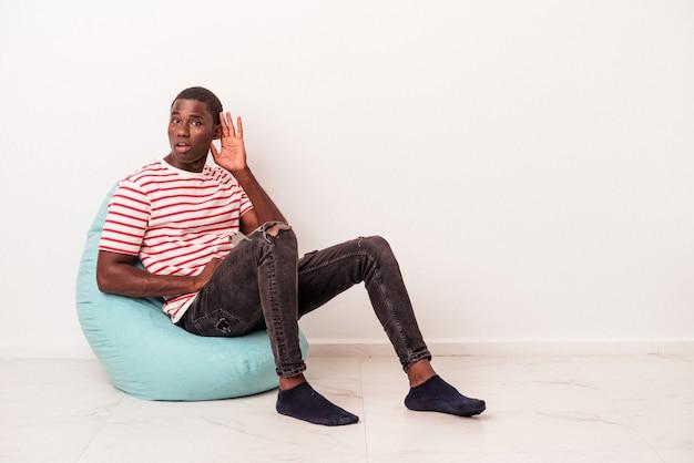 Jovem afro-americano sentado em um puff isolado no fundo branco, tentando ouvir uma fofoca.