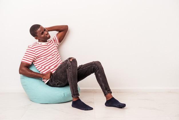 Jovem afro-americano sentado em um puff isolado no fundo branco, tocando a parte de trás da cabeça, pensando e fazendo uma escolha.