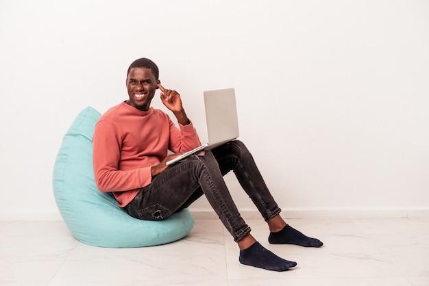 Jovem afro-americano sentado em um puff usando laptop isolado no fundo branco, cobrindo as orelhas com as mãos.