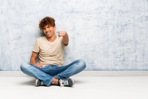 Jovem afro-americano sentado no chão aponta o dedo para você com uma expressão confiante