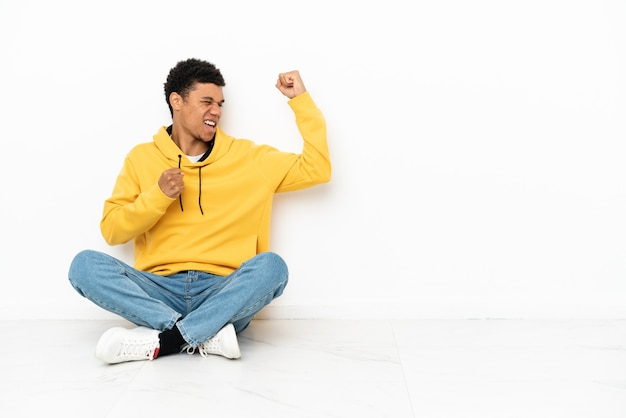 Jovem afro-americano sentado no chão, isolado no fundo branco, comemorando uma vitória